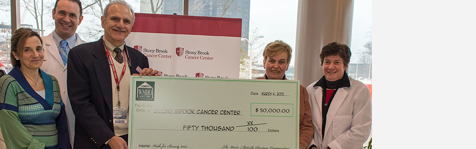 Yusuf Hannun, MD, Director, Stony Brook University Cancer Center, accepts a check from Gloria Rocchio, President, Ward Melville Heritage Organization